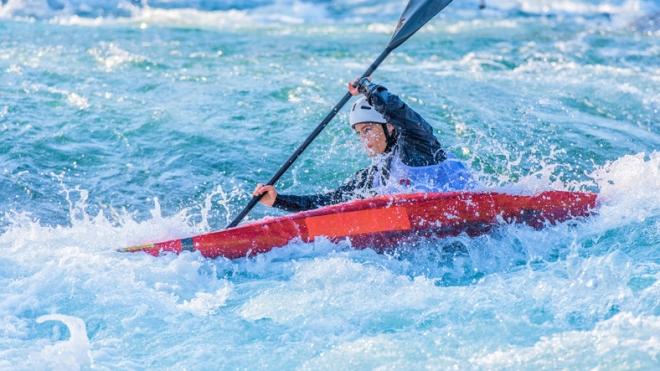 Female kayaker paddling in whitewater